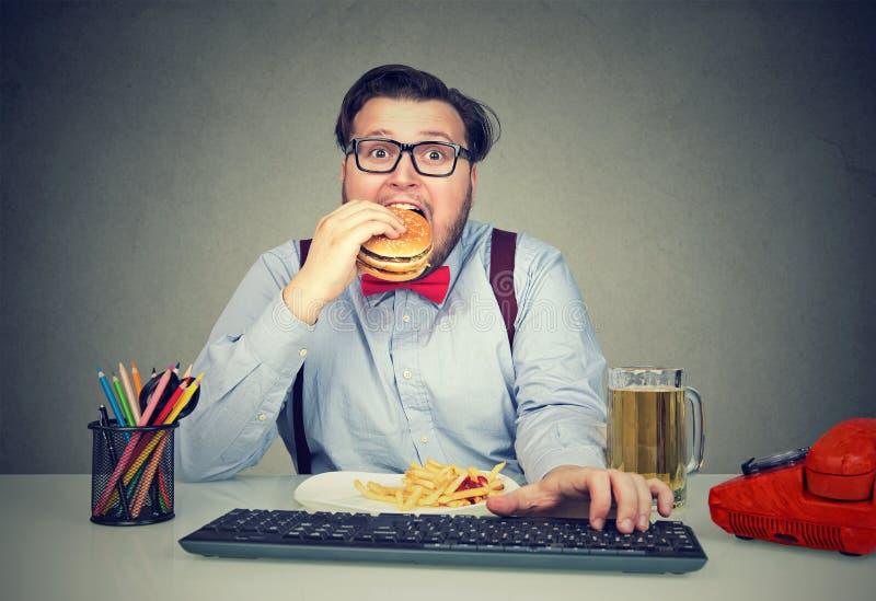 饥饿的食人的快餐在工作 免版税图库摄影