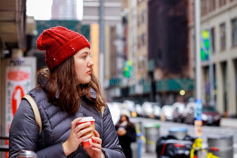 饮料和人概念-从纸杯的愉快的年轻十几岁的女孩饮用的咖啡在城市街道上 图库摄影