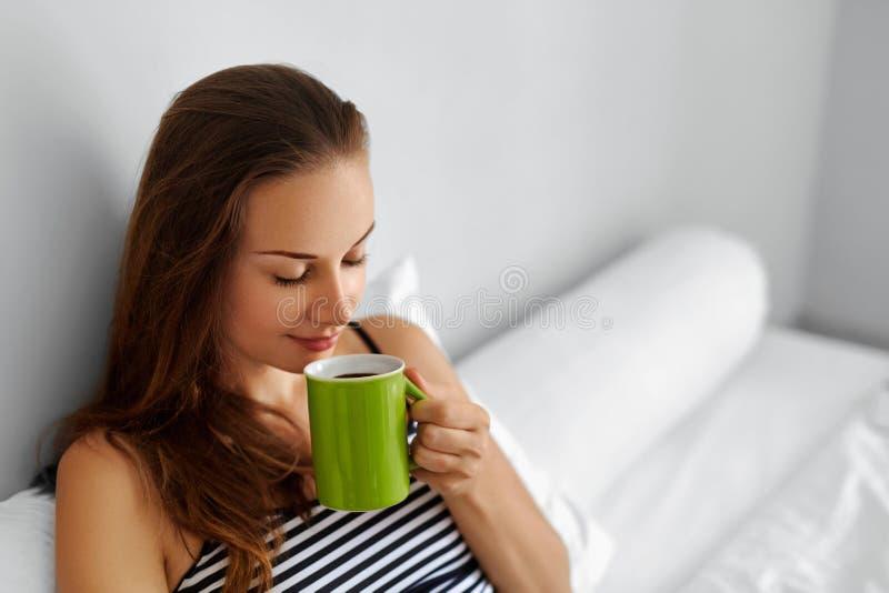 饮料早晨咖啡 妇女饮用的饮料在床上 健康生活方式 免版税图库摄影