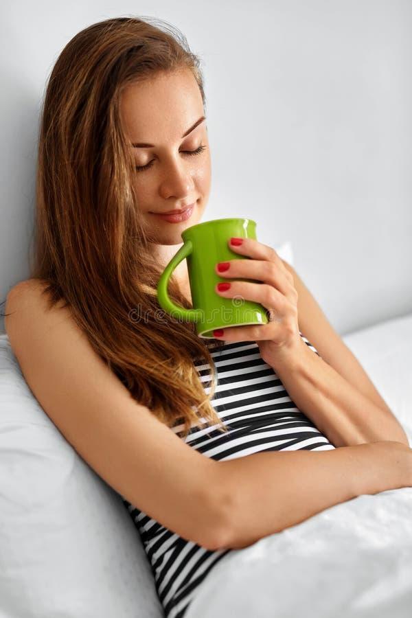 饮料早晨茶 妇女饮用的饮料在床上 健康Lifes 库存图片