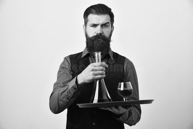 饮料概念 有胡子的人拿着在白色背景的科涅克白兰地 葡萄酒绒面革皮革背心服务的男服务员 免版税库存图片