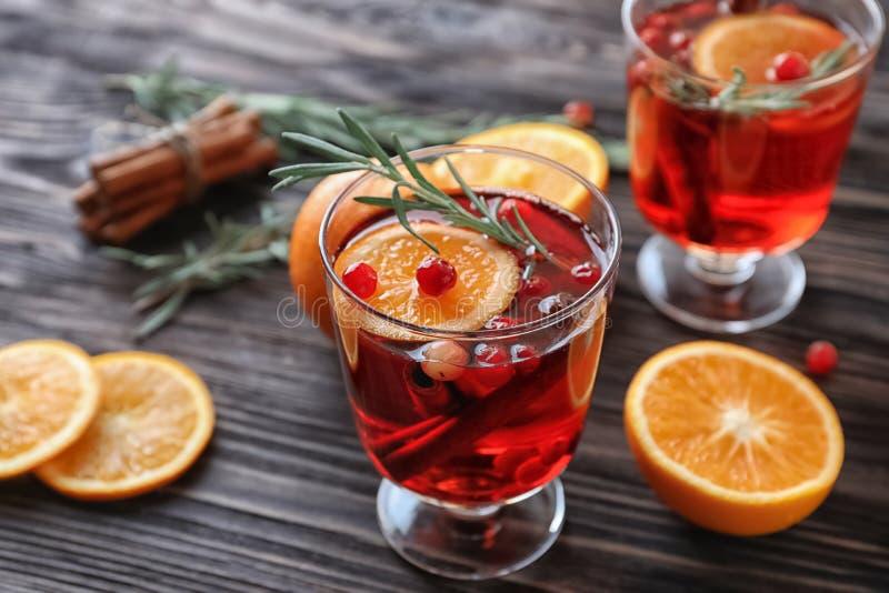 饮料用桂香、桔子和蔓越桔在玻璃在木桌上 免版税图库摄影