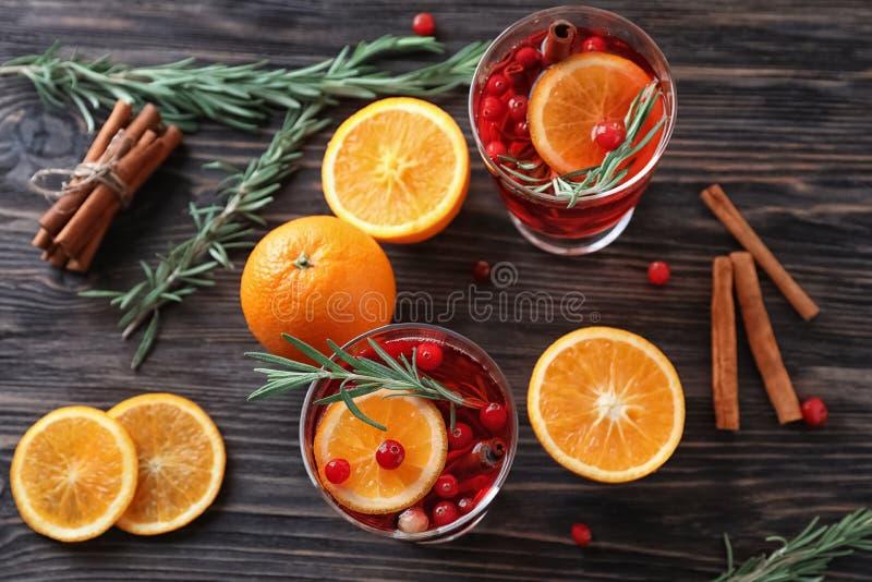 饮料用桂香、桔子和蔓越桔在玻璃在木桌上 免版税库存照片