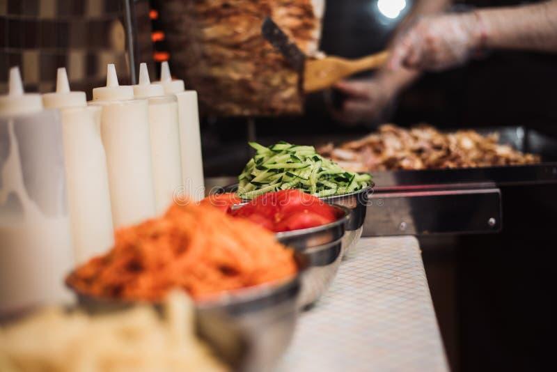 饮料用蕃茄、黄瓜、韩国红萝卜和薯条、调味汁盘在kebabs背景和油煎的鸡肉 免版税库存图片