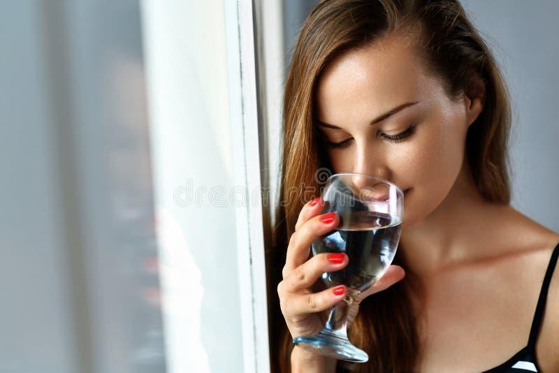 饮料水 微笑的妇女饮用水 饮食 健康生活方式 免版税图库摄影