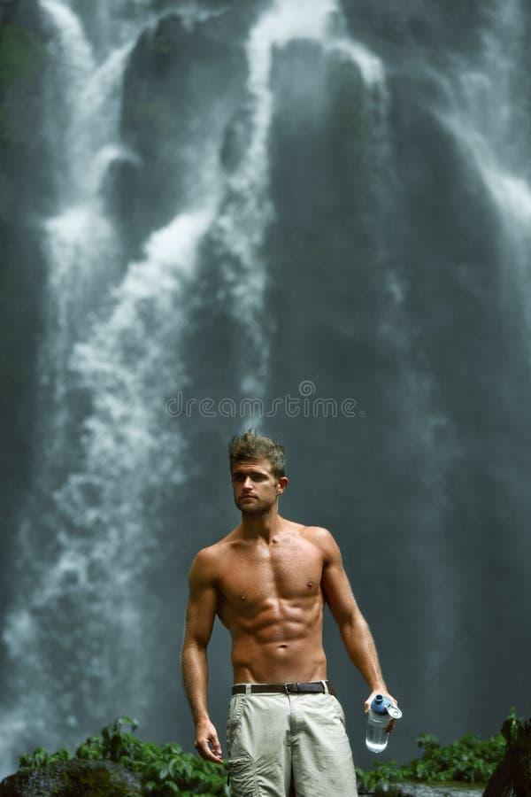 水饮料 有性感的身体的健康人在瀑布附近 健康 免版税库存照片