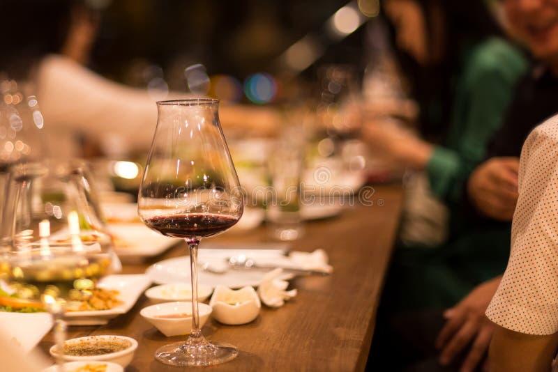 饮用小组的朋友晚餐和红葡萄酒 库存照片