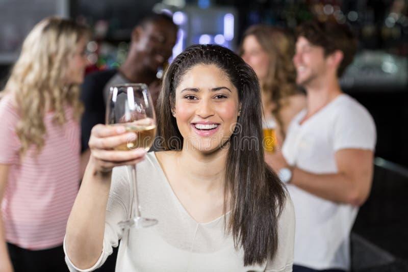 饮用微笑的女孩一杯与她的朋友的酒 免版税库存图片