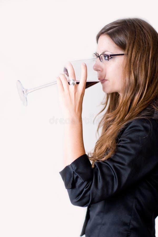 饮用的侧视图酒妇女 免版税库存照片