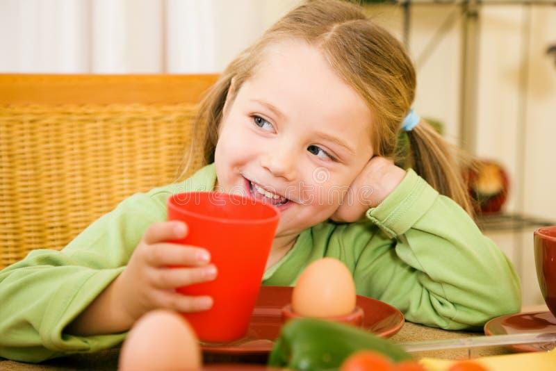 饮用的女孩她的少许牛奶 免版税库存图片