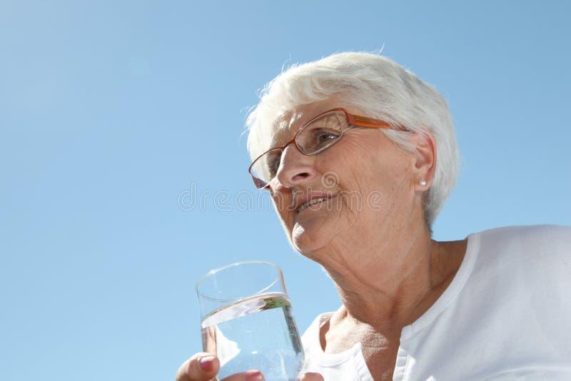 饮用的年长水妇女 库存图片