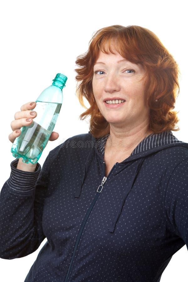 饮用的愉快的查出的成熟水妇女 库存照片
