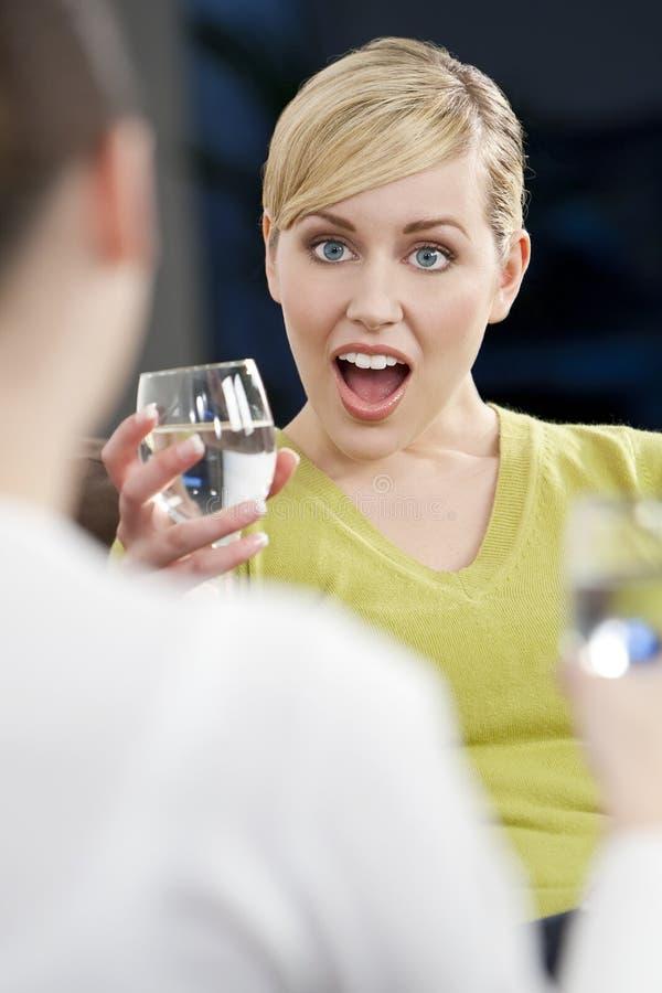 饮用的朋友惊奇的妇女年轻人 库存图片