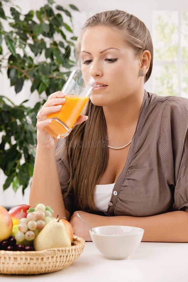 饮用的汁液橙色妇女年轻人 免版税库存图片