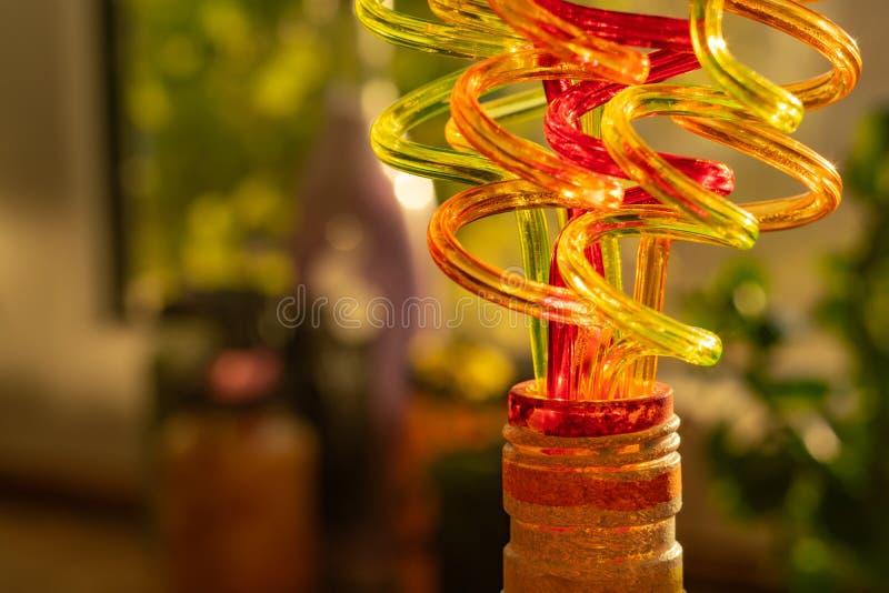 饮用的汁液的色的管在一个装饰瓶的脖子 弯曲以螺旋的形式 免版税库存照片