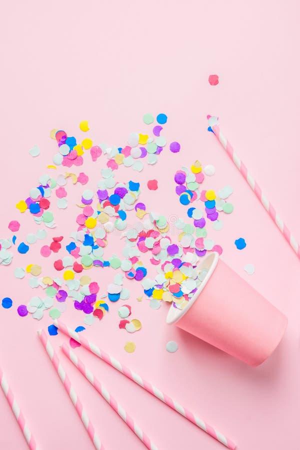 饮用的纸杯镶边了在紫红色的背景驱散的秸杆五颜六色的五彩纸屑 平的位置构成 生日聚会孩子 库存照片