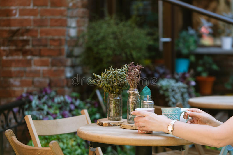 饮用的茶 拿着杯子饮料的妇女,当坐在caf时 免版税库存图片
