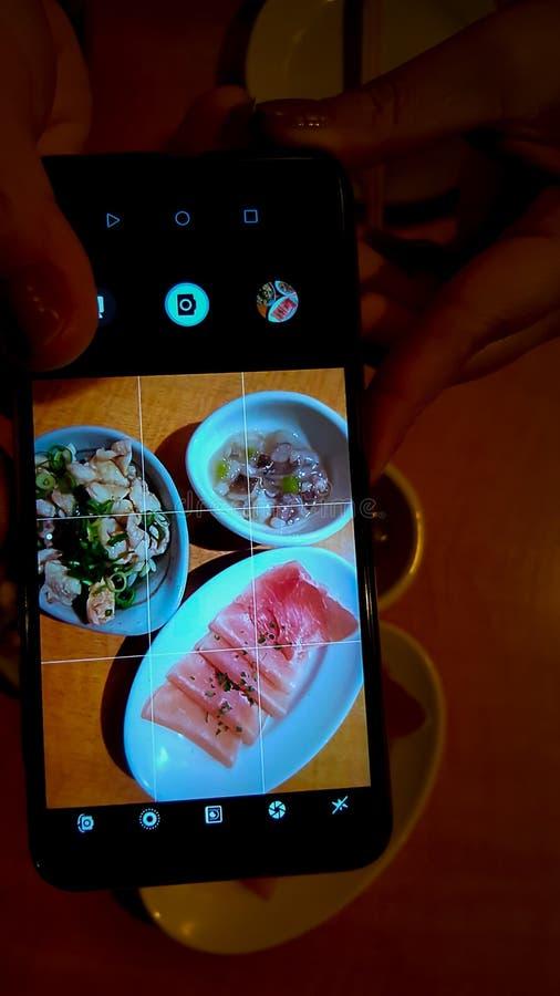 饮者的食物是被发酵的鸡,火腿,并且在白色盘的山葵乌贼照片是在流动手机屏幕后 免版税图库摄影