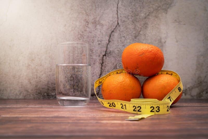 饮食、测量的磁带和饮用水的新鲜水果在木桌上 饮食和健康生活方式的概念 免版税图库摄影
