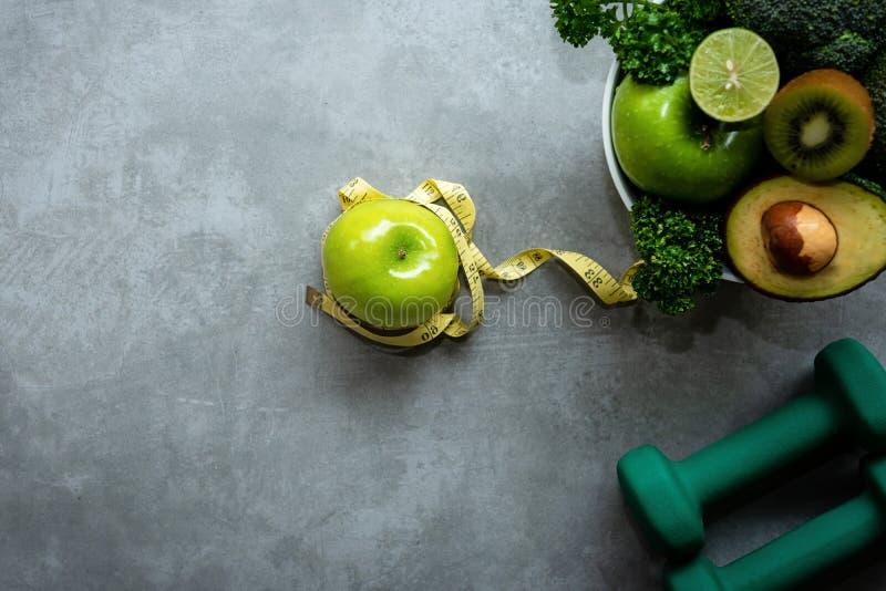 饮食和健康生活损失重量概念 绿色苹果和重量标度与新鲜蔬菜和运动器材的措施轻拍w的 免版税库存图片