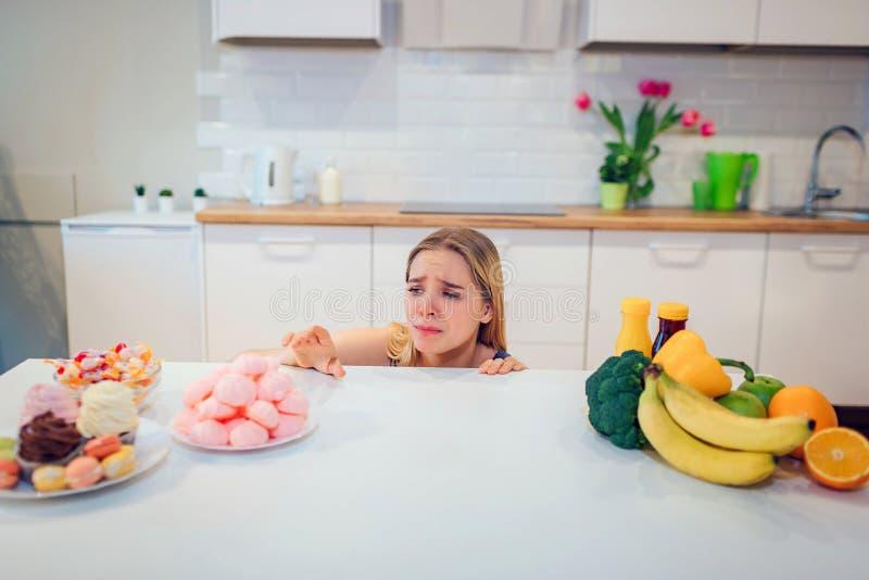 饮食奋斗 选择在新鲜水果菜或甜点之间的蓝色T恤杉的年轻哀伤的妇女在厨房里 选择 免版税库存图片