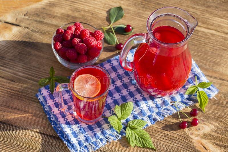 饮食戒毒所饮料用柠檬汁、红色草莓、樱桃和莓在清楚的水中与冰 免版税图库摄影