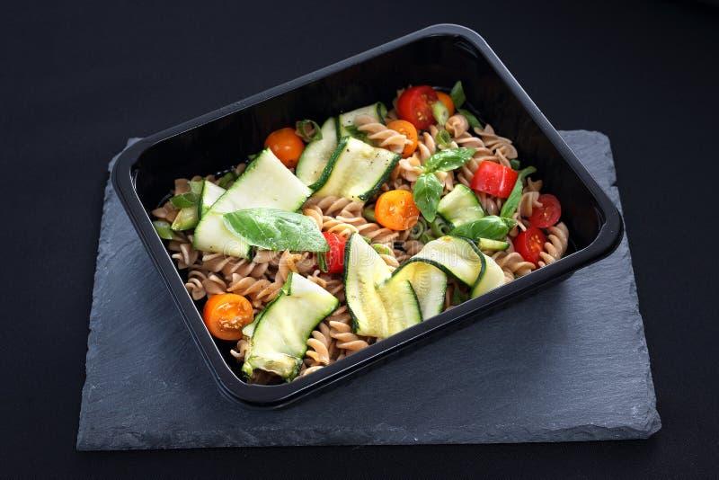 饮食承办酒席 意大利面制色拉用夏南瓜和蕃茄在一个黑色的盘子服务 免版税图库摄影
