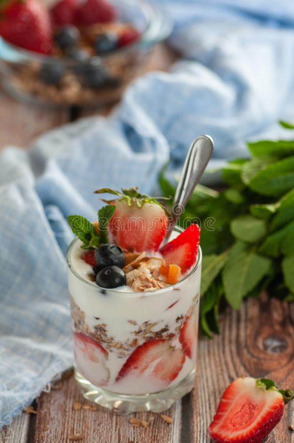 饮食早餐A杯酸奶充满草莓、蓝莓和格兰诺拉麦片 免版税库存图片