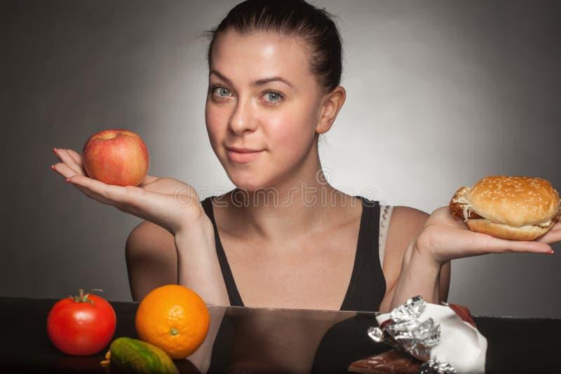 饮食概念:拿着汉堡和苹果的妇女 免版税图库摄影