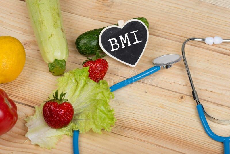 饮食概念-在心脏形状的黑板与文本BMI身体容积指数、听诊器、蔬菜、水果和莓果的 免版税图库摄影