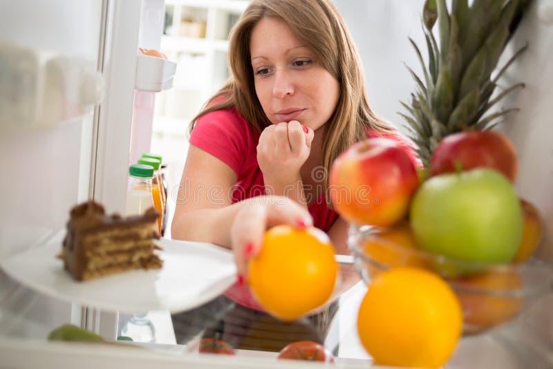 饮食的女性在困境是否吃巧克力蛋糕或orang 免版税库存图片