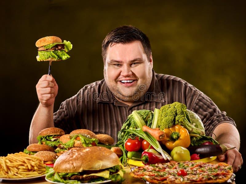 饮食肥胖人做出在健康和不健康的食物之间的选择 免版税库存照片