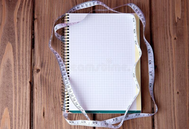 饮食计划概念 测量的磁带和纸笔记本有题字用餐计划的在蓝色木背景 饮食健康减肥 免版税库存图片