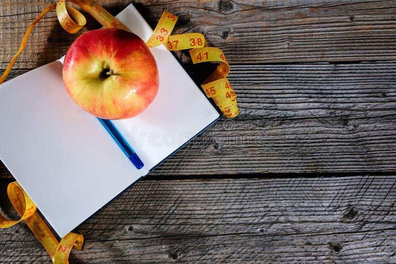 饮食计划 笔记本c题字-饮食、一卷测量的磁带、苹果和笔 库存图片
