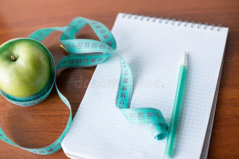 饮食计划 笔记本c题字-饮食、一卷测量的磁带、苹果和笔 库存照片