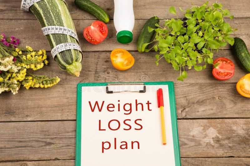 饮食计划-西葫芦、剪贴板有文本的& x22; 减重plan& x22; 菜和测量的轻拍 库存图片