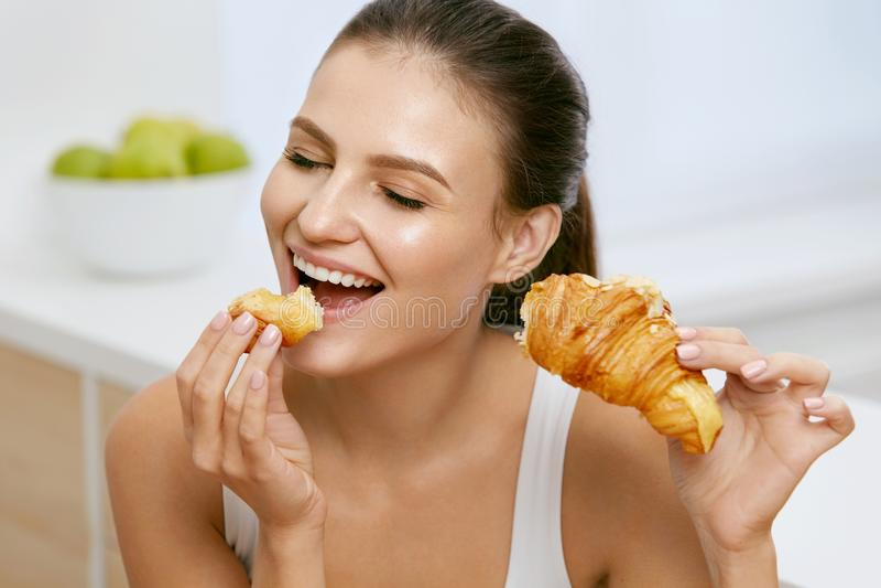 饮食 吃新月形面包早餐的愉快的妇女 免版税库存照片