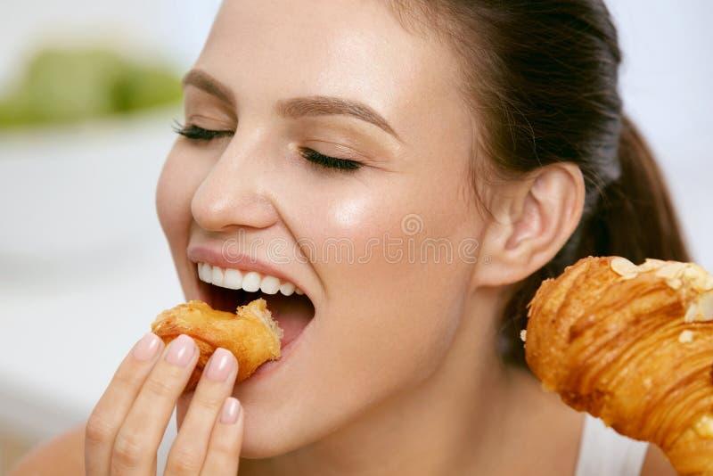 饮食 吃新月形面包早餐的愉快的妇女 免版税库存图片