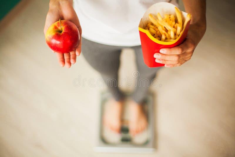 饮食 在拿着不健康的垃圾食品的秤的妇女测量的体重 查出的损失评定躯干重量白人妇女 肥胖病 顶视图 免版税图库摄影