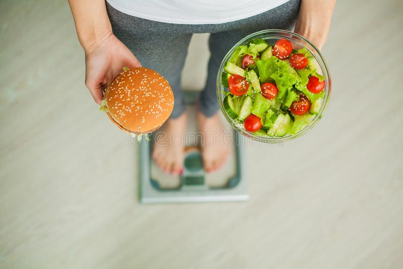 饮食 在秤藏品汉堡和沙拉的妇女测量的体重 甜点是不健康的速食 节食 免版税库存照片