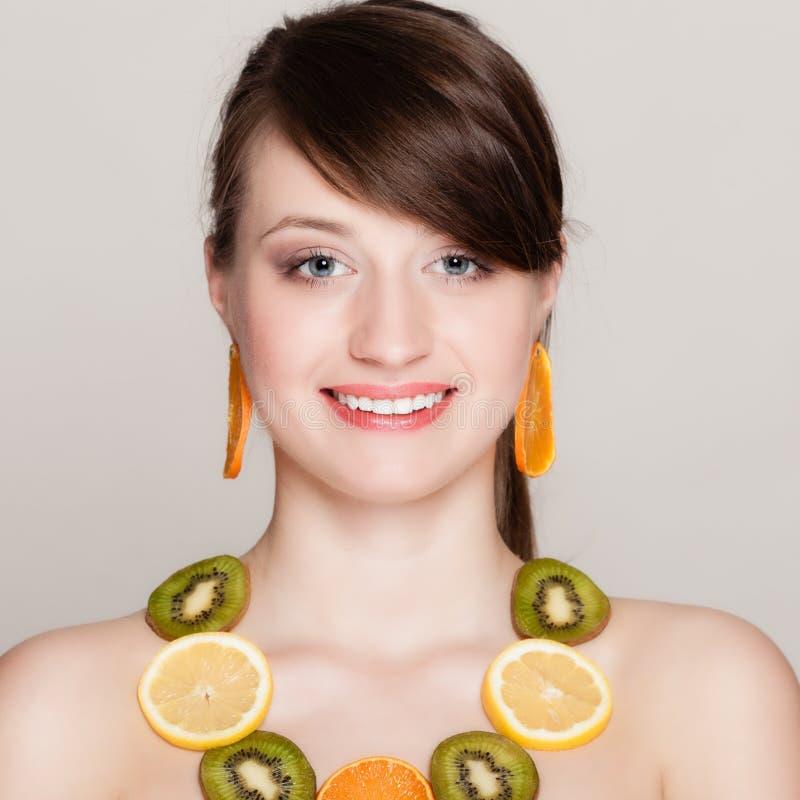 饮食 有新鲜的柑橘水果项链的女孩  免版税图库摄影