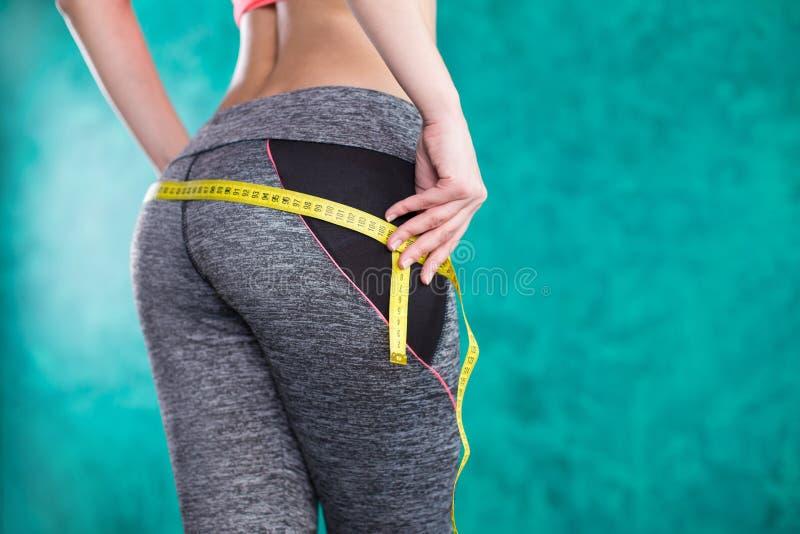 饮食 递有磁带的测量的腰部 绿松石背景的适合和健康妇女 免版税图库摄影