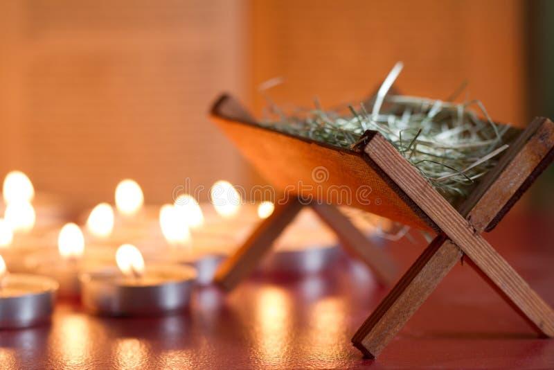 饲槽诞生场面蜡烛和圣经在夜摘要背景中 库存图片
