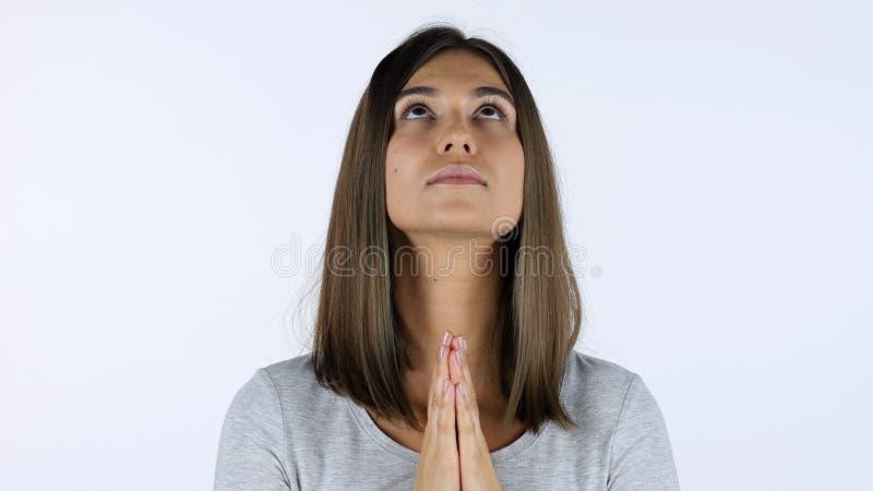 饶恕的,白色背景祈祷的美丽的女孩在演播室 免版税图库摄影