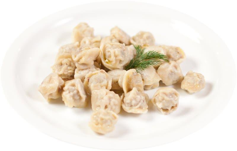 饺子和荷兰芹-俄国pelmeni -意大利馄饨-在被隔绝的白色板材 图库摄影