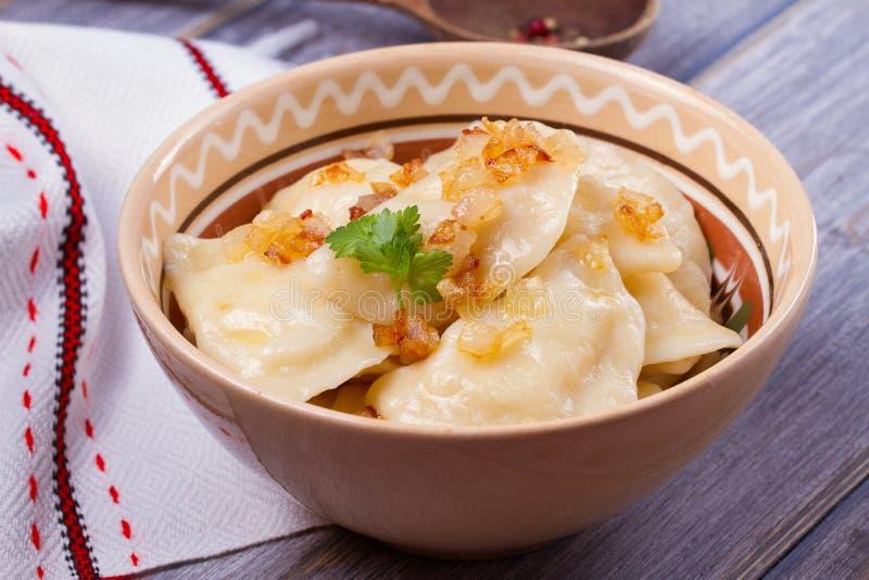 饺子,充满土豆泥-蔬菜菜肴 Varenyky, vareniki, pierogi, pyrohy在木桌上的一个碗 免版税库存照片