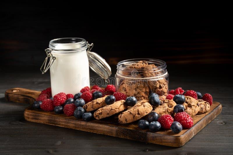 饼干、莓果和牛奶在木底部,侧视图 免版税库存图片