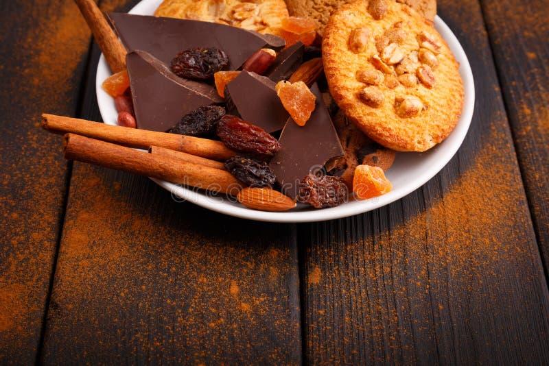 饼干,在一块板材的黑巧克力在桌上 在板材附近洒与桂香 侧视图 免版税库存照片