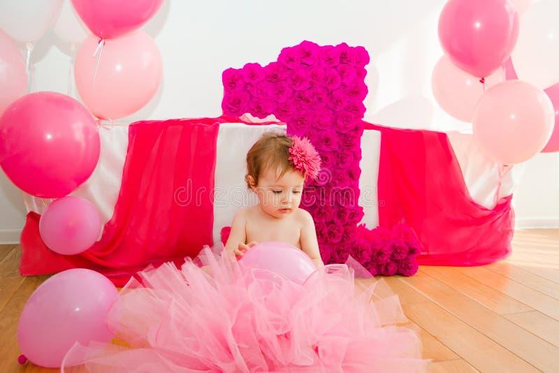 首先生日 蓬松桃红色裙子的婴孩,有气球和双的 库存图片