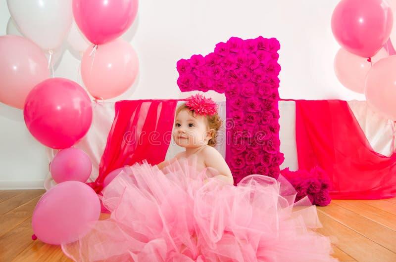 首先生日 蓬松桃红色裙子的婴孩,有气球和双的 免版税库存图片